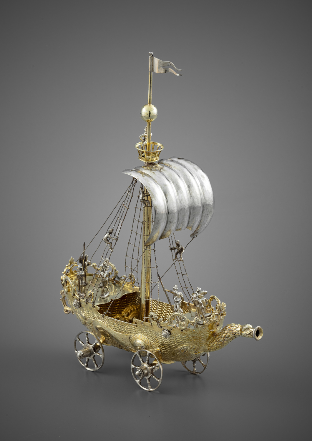 A silver and silver-gilt drinking cup in the shape of a vessel on wheels - Galerie Kugel